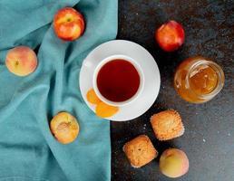 Taza de té con pasas en bolsita de té y melocotones sobre tela con mermelada de melocotón sobre fondo negro y marrón