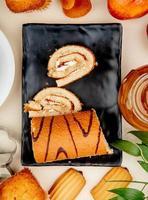 Vista superior del rollo cortado y en rodajas en placa con mermelada de melocotón galletas cupcake alrededor sobre fondo blanco.