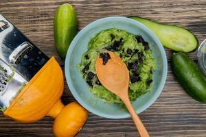 Vista superior del tazón de ensalada de verduras con cuchara de madera y pepinos con rallador sobre fondo de madera foto