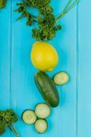 Vista superior de verduras como cilantro pepino con limón sobre fondo azul. foto