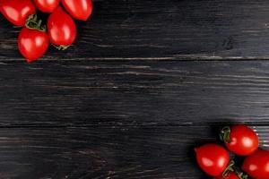 Top view of tomatoes on left and right sides and wooden background with copy space