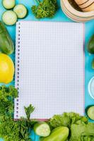 Top view of vegetables as cucumber coriander lettuce with lemon and garlic crusher and note pad on blue background with copy space
