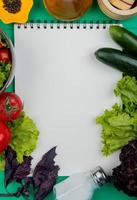 Top view of vegetables as basil tomato lettuce cucumber with salt and black pepper with note pad on green background with copy space