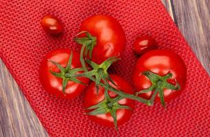 Vista superior de tomates sobre tela roja y fondo de madera