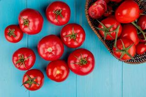 Top view of tomatoes with basket of tomatoes on blue background