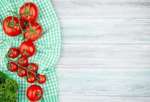 Top view of tomatoes on plaid cloth with coriander on wooden background with copy space