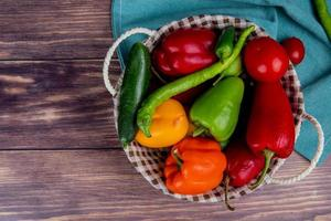 Top view of vegetables as cucumber pepper tomato in basket on blue cloth and wooden background with copy space