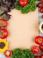 Vista superior de verduras como albahaca, tomate, cilantro con pimienta negra y trituradora de ajo con bloc de notas sobre fondo de madera con espacio de copia foto