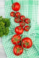 Top view of tomatoes on plaid cloth with coriander on wooden background photo