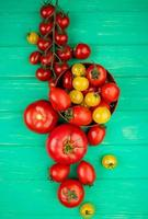Top view of tomatoes in bowl with other ones on green background photo