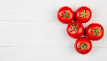 Top view of tomatoes on right side and wooden background with copy space