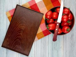 Top view of tomatoes with knife in bowl and empty tray on cloth on wooden background