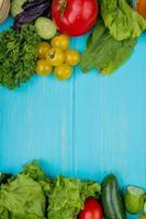Top view of vegetables as coriander basil tomato spinach lettuce cucumber on blue background with copy space