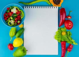 Top view of vegetables as cucumber pepper tomato lettuce with black pepper seeds and sliced peppers with note pad on blue background with copy space