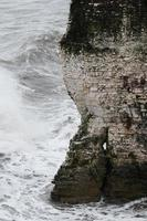 Water waves hitting rocky mountain during daytime