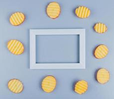 Top view of potato slices around frame on blue background with copy space