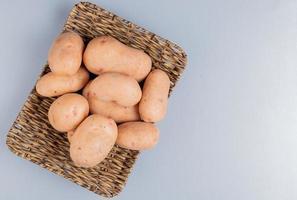Vista superior de patatas en placa sobre fondo azul con espacio de copia foto