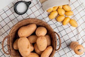 Vista superior de las patatas en la canasta con mantequilla, sal, pimienta negra sobre fondo de tela escocesa