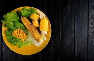 Vista superior de maíz cortado y entero y semillas de maíz con lechuga en placa en el lado izquierdo y fondo negro con espacio de copia