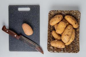 Vista superior de la patata y el cuchillo en la tabla de cortar con otros en la placa de la cesta sobre fondo blanco.
