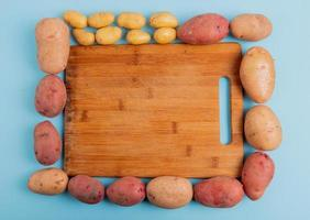 Top view of potatoes around cutting board on blue background photo