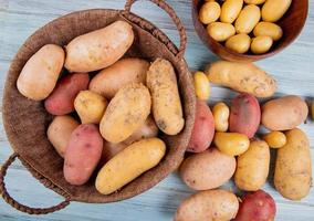 Top view of potatoes in basket with new ones in bowl and others of different types on wooden background photo