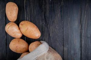 Top view of potatoes spilling out of sack on wooden background with copy space photo