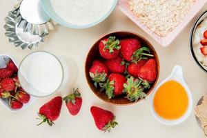 Vista superior de fresas en un tazón y un vaso de leche y mantequilla derretida con harina y avena sobre fondo blanco.