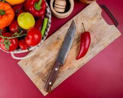 Vista superior de pimientos y cuchillo sobre una tabla para cortar