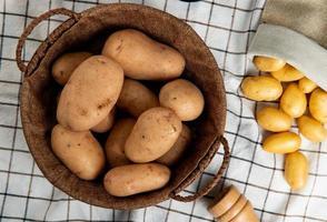 Vista superior de las patatas en la canasta con otros derramándose del saco sobre fondo de tela escocesa foto