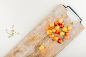 top view of cherries on cutting board with stems on white background