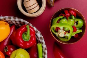 Top view of pepper slices in bowl with vegetables as pepper tomato in basket with garlic crusher on bordo background
