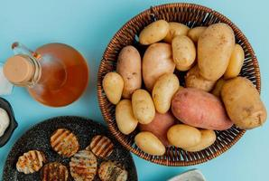 top view of potatoes in basket and fried ones in frying pan with melted butter on blue background
