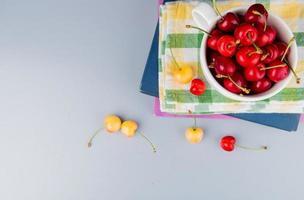 Vista superior de cerezas rojas en taza sobre tela y libros con cerezas amarillas sobre fondo azul con espacio de copia foto