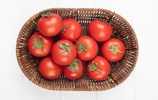 Vista superior de los tomates en la canasta sobre fondo blanco.