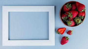 Top view of strawberries in bowl and white frame on blue background with copy space photo