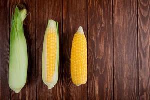 Vista superior de mazorcas de maíz con cáscara en el lado izquierdo y fondo de madera con espacio de copia