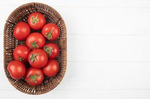 Top view of tomatoes in basket on left side and white background with copy space