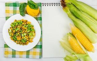 Vista superior de la ensalada de maíz sobre tela y limón con mazorcas de maíz y bloc de notas sobre fondo de madera foto