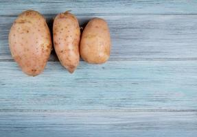 Top view of russet potatoes on left side and wooden background with copy space photo