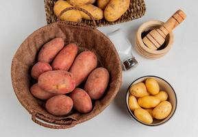 Top view of potatoes in basket and in plate with salt black pepper on white background photo