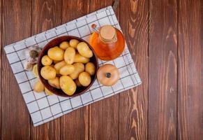 Vista superior de las patatas en un tazón con ajo, limón, sal y mantequilla sobre tela escocesa y fondo de madera con espacio de copia