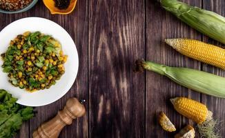 Vista superior de la ensalada de maíz con lechuga de maíz cortado y entero sobre fondo de madera foto