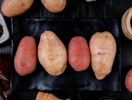Top view of potatoes in plate and on wooden background