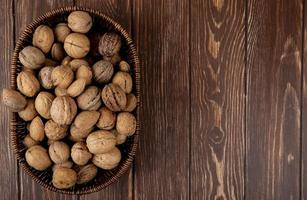 top view of whole walnuts in a wicker basket on wooden background with copy space