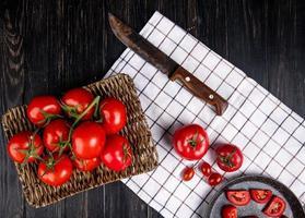 Vista superior de los tomates en el plato de la cesta con otros sobre tela y cuchillo sobre fondo de madera