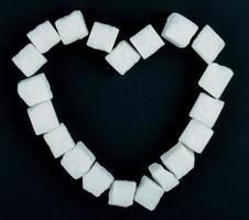 Vista superior de terrones de azúcar dispuestos en forma de corazón sobre fondo negro foto