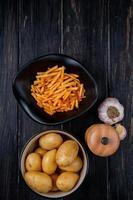 Vista superior de papas en tazones como fritos y crudos enteros con sal y ajo sobre fondo de madera