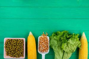 top view of corns and corn seeds with green peas lettuce on green background with copy space