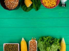 top view of corns and corn seeds with green peas salt lettuce spinach on green background with copy space